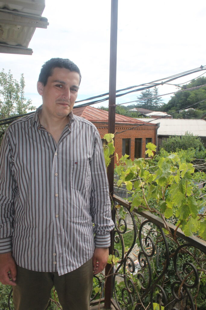 Man at the balcony with grape leaves